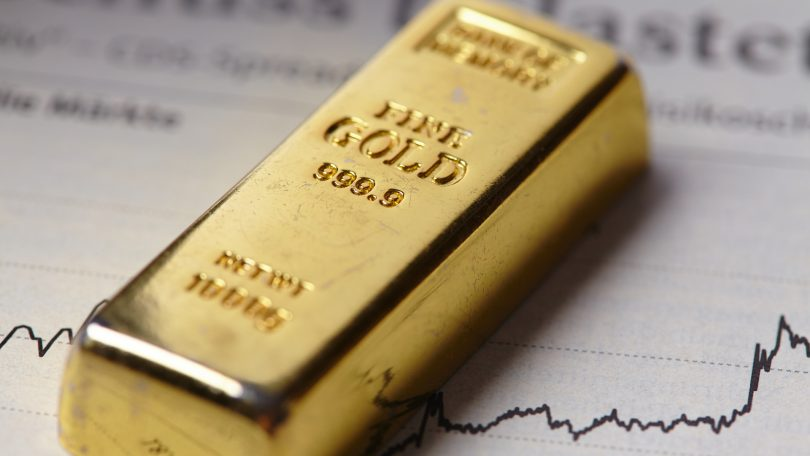 gold bar for investing and stock chart